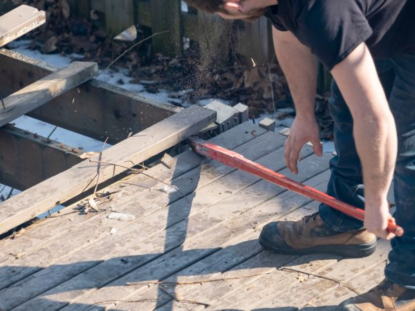 Man,Dismantling,An,Old,Wooden,Deck,With,A,Red,Crowbar